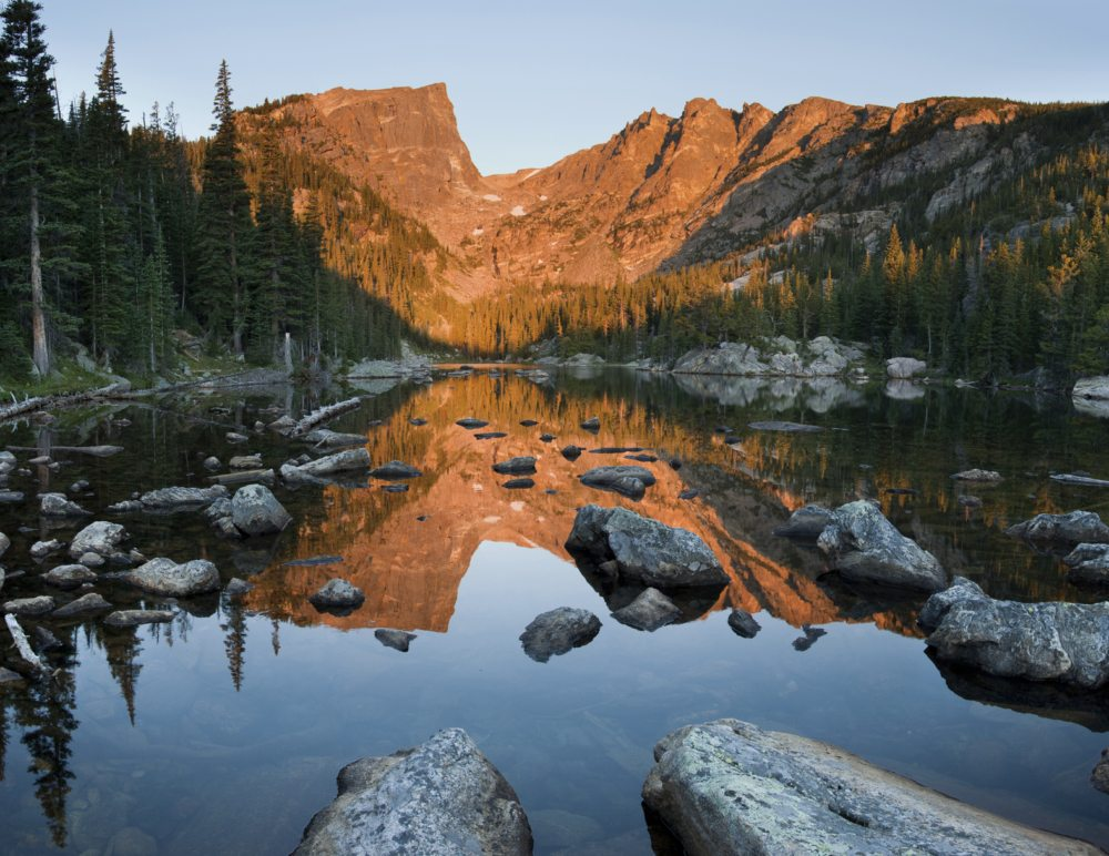 """Sunrise lights up Hallet Peak with a warm alpenglow.  In the foreground, a calm Dream Lake perfectly reflects the scene."""