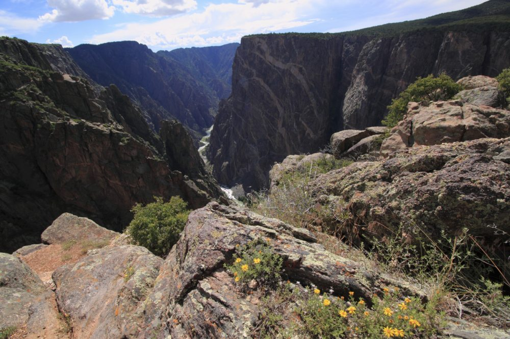 Mid-Day at the Black Canyon of the Gunnison National Park, Colorado. This cliff is the Painted Wall, the tallest vertical cliff in Colorado, at 2,722 feet. Harsh sunlight reflects off of the Gunnison River below.