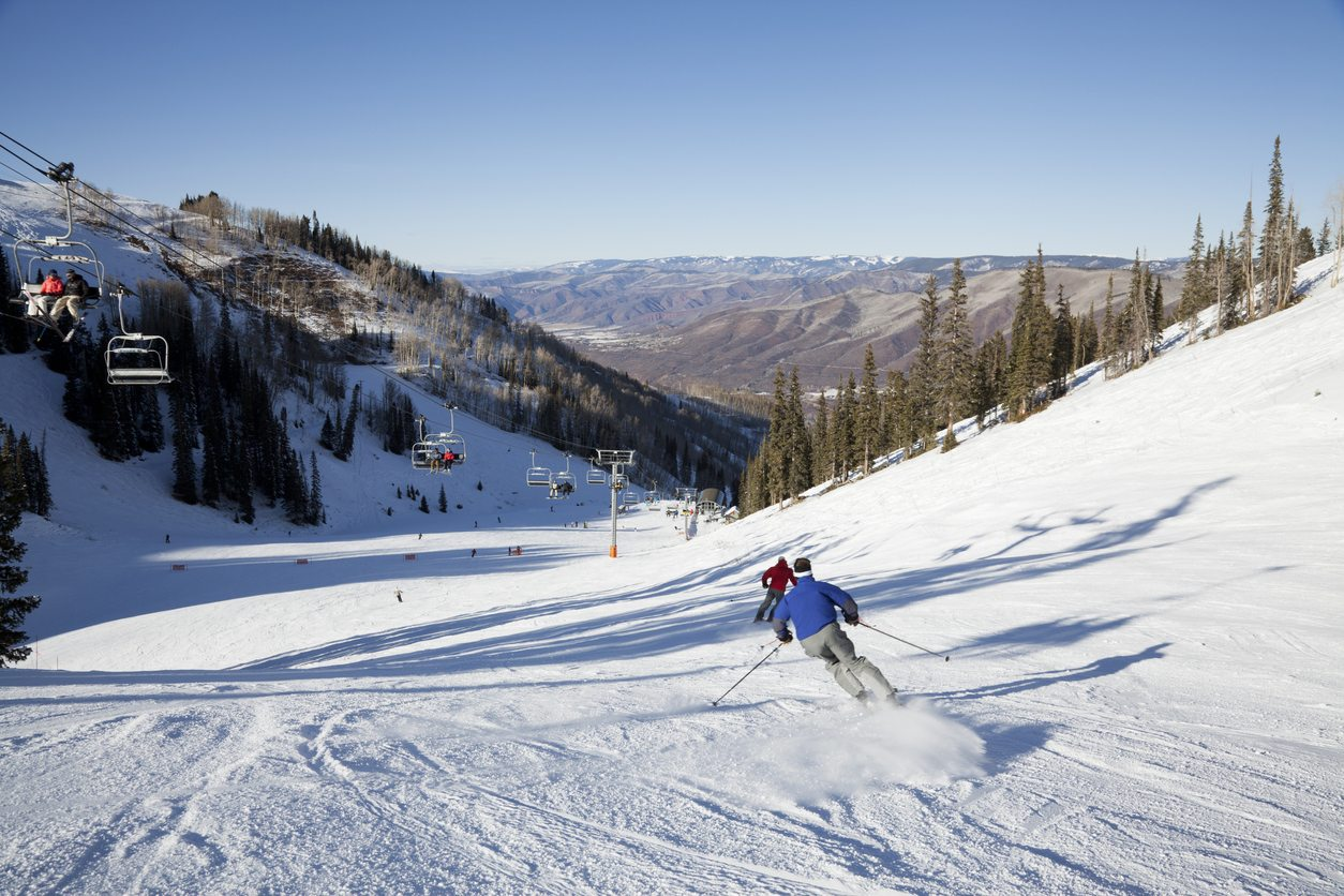 A pair of fast skiers rocket down a groomed trail on Ajax Mountain at Aspen Colorado.