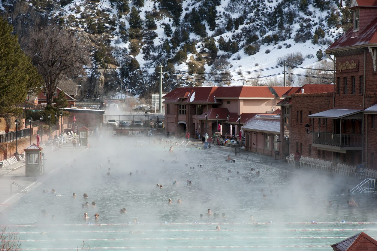 Glenwood Springs, United States - December 28, 2013: Glenwood Hot Springs in Winter - The historic Glenwood Hot Springs pool is 104 degrees year round, so on a cold winter morning, with snow covered moutains, steam rises off the pool's surface