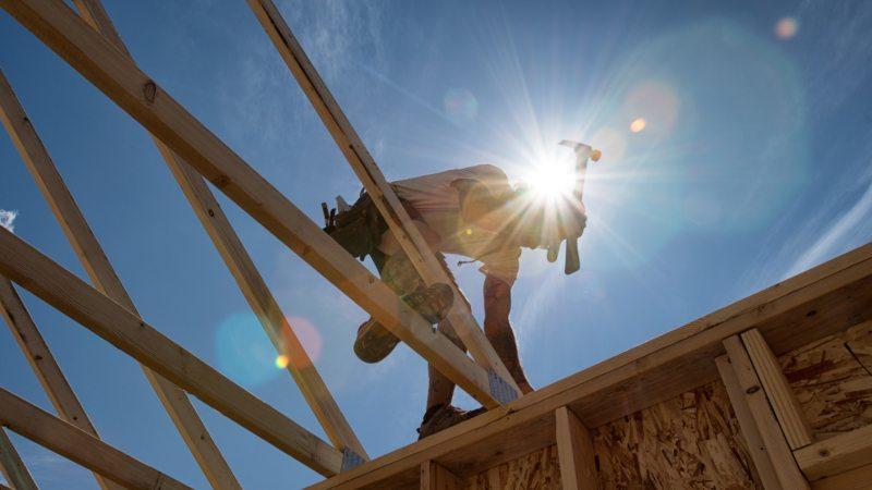 Construction worker positioning a piece of frame work, a roof truss onto a building structure against a sunny blue sky.