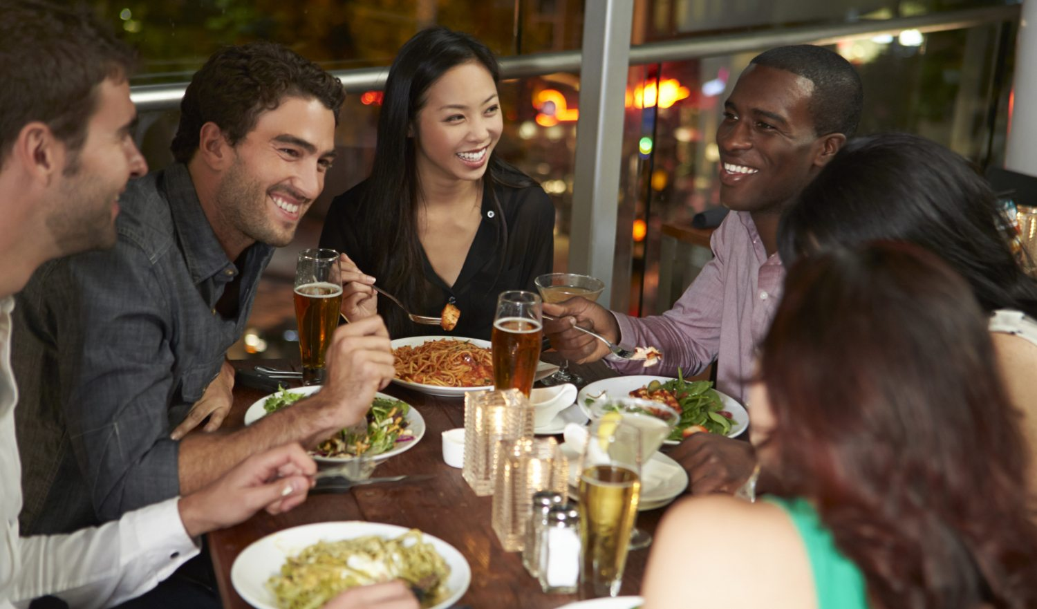 Group Of Friends Enjoying Evening Meal In Restaurant Smiling And Laughing Together.
