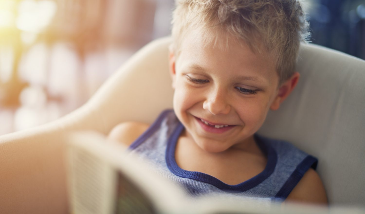 Closeup portrait of a little boy aged 6 reading a book. The boy is sitting in an armchair and is smiling, showing a missing tooth.