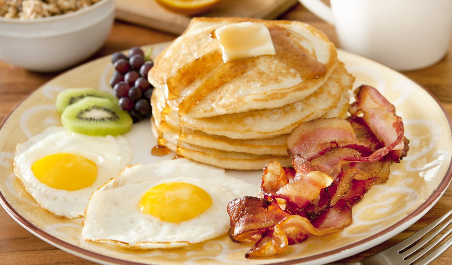 """Closeup of a breakfast plate with pancakes, eggs, bacon and fruit.Related Images:"""