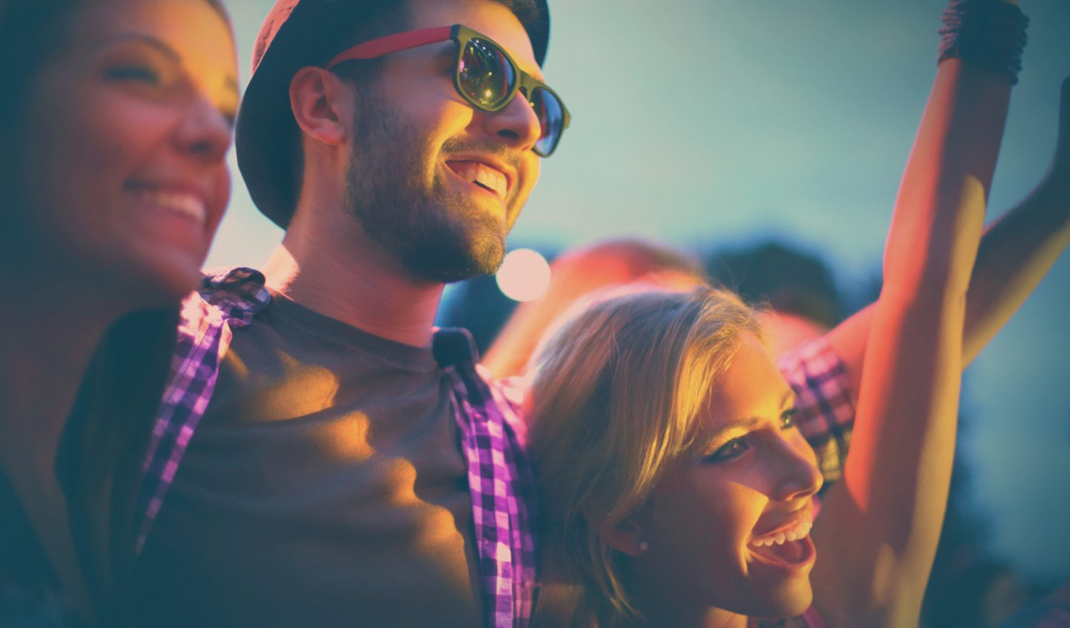 Group of friends enjoying a concert.Two girls and a guy standing embraced,looking at stage and cheering.All of them laughing,the guy is wearing sunglasses.It's summer sunset