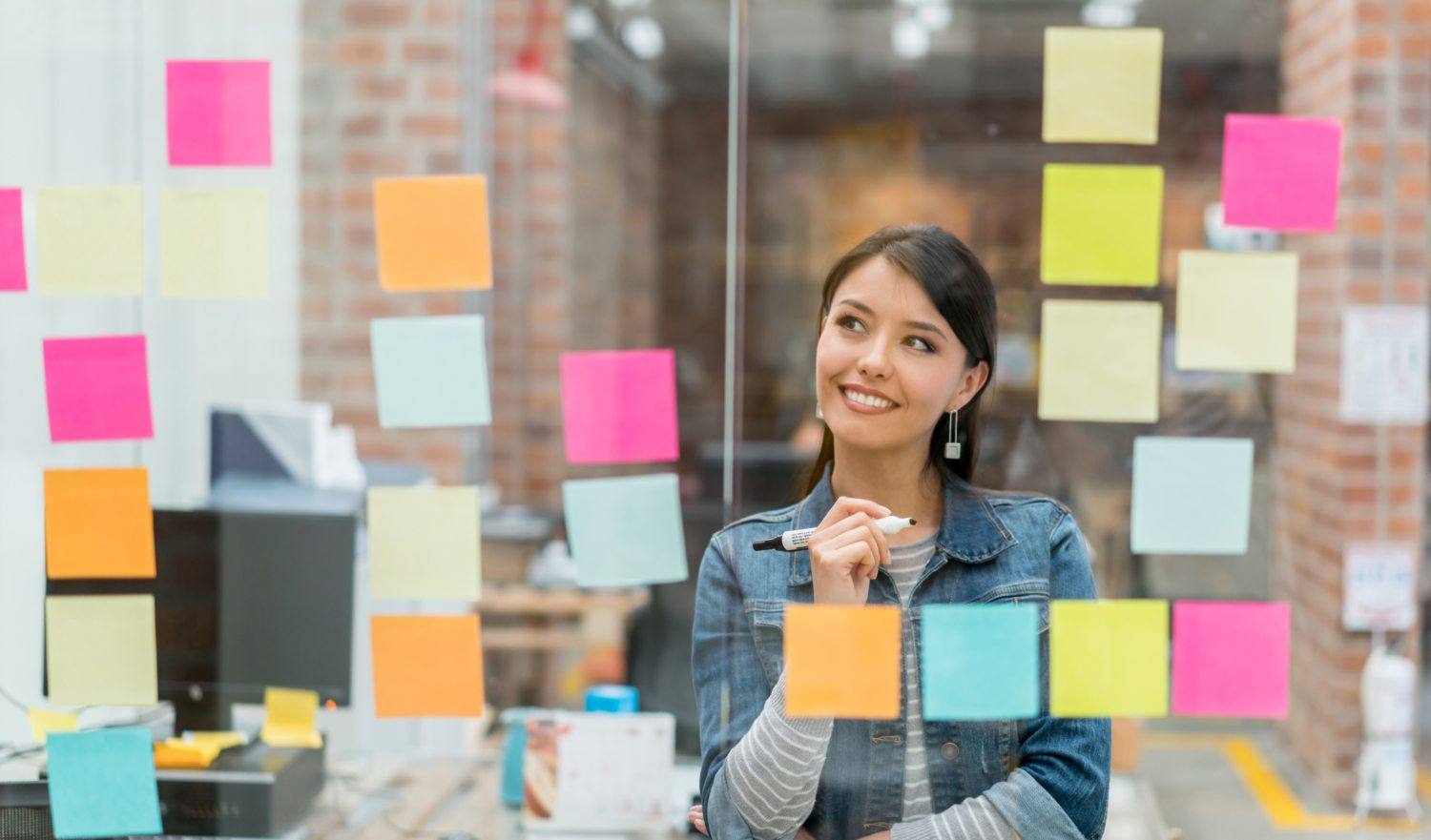 Latin American woman thinking of creative sales ideas at the office to put in a wall chart