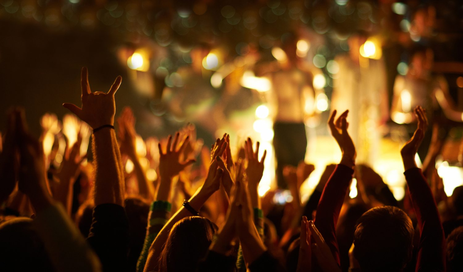 Audience with hands in the air at a music festival. Unrecognizable people.