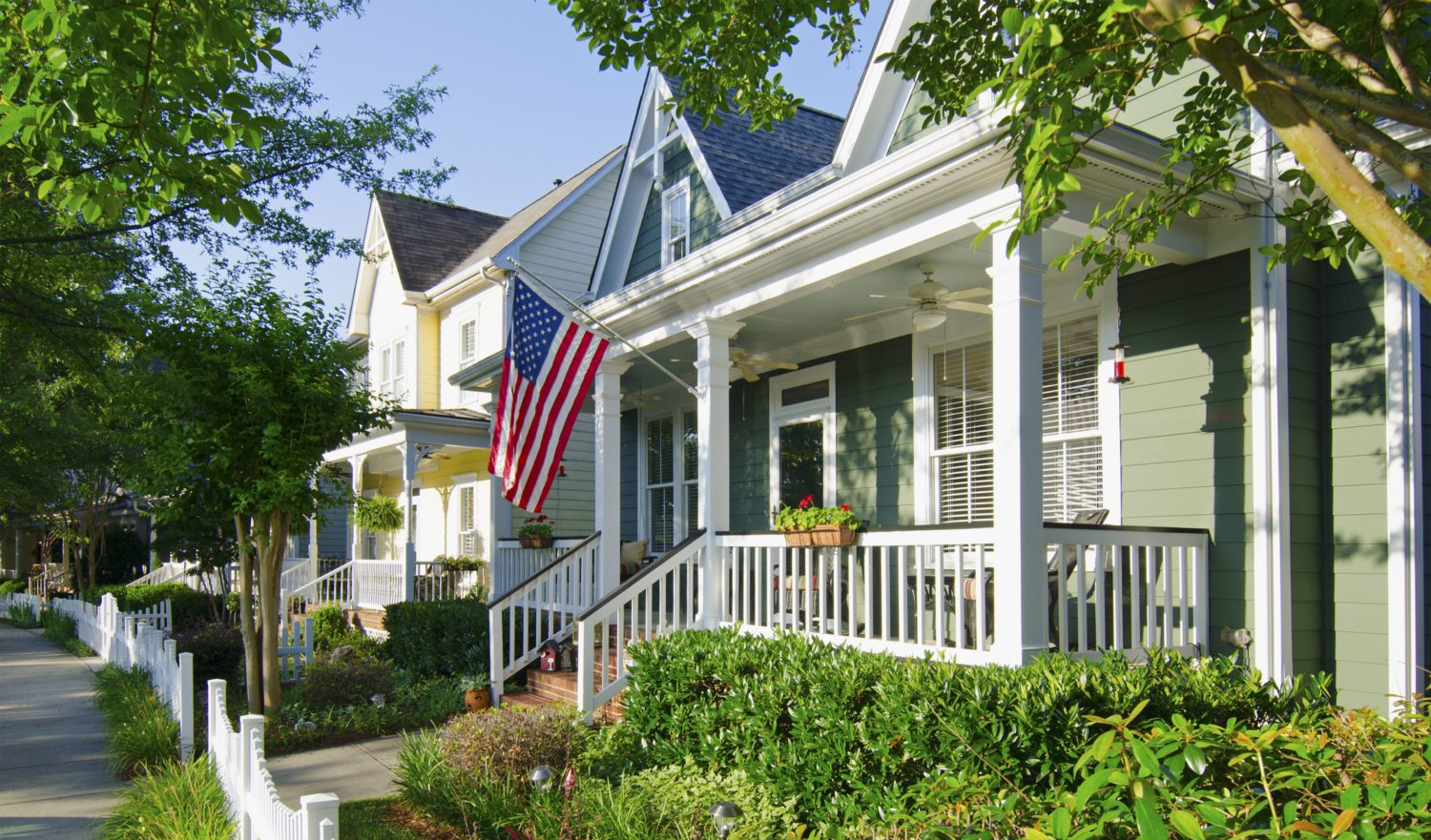 The American Dream of a house in a nice neighborhood with a white picket fence is captured in this iconic image.