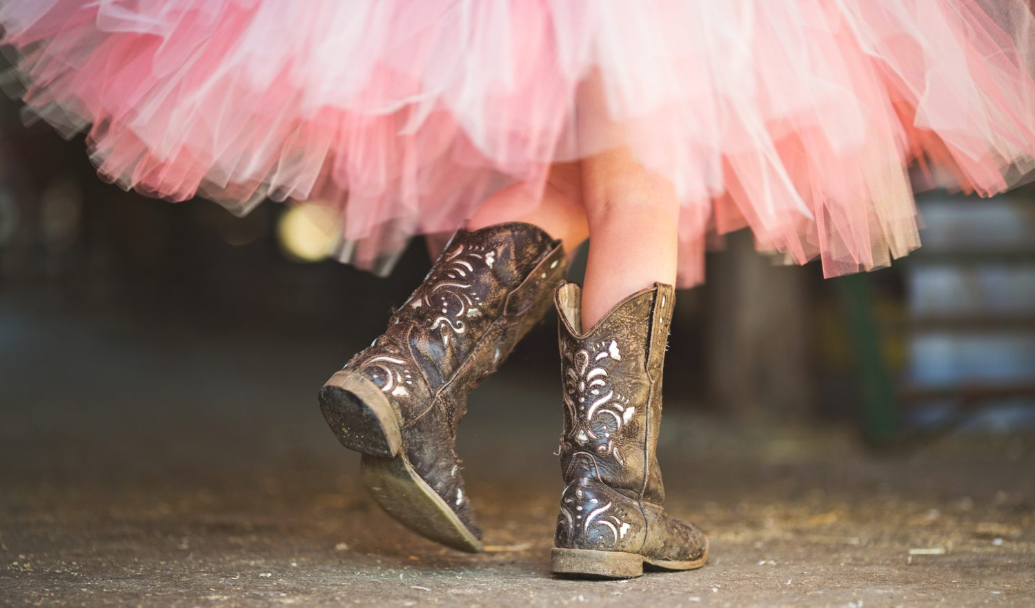 Princess Cowgirl. Little cowgirl walking though a barn in her boots and pink tutu in the afternoon sun.