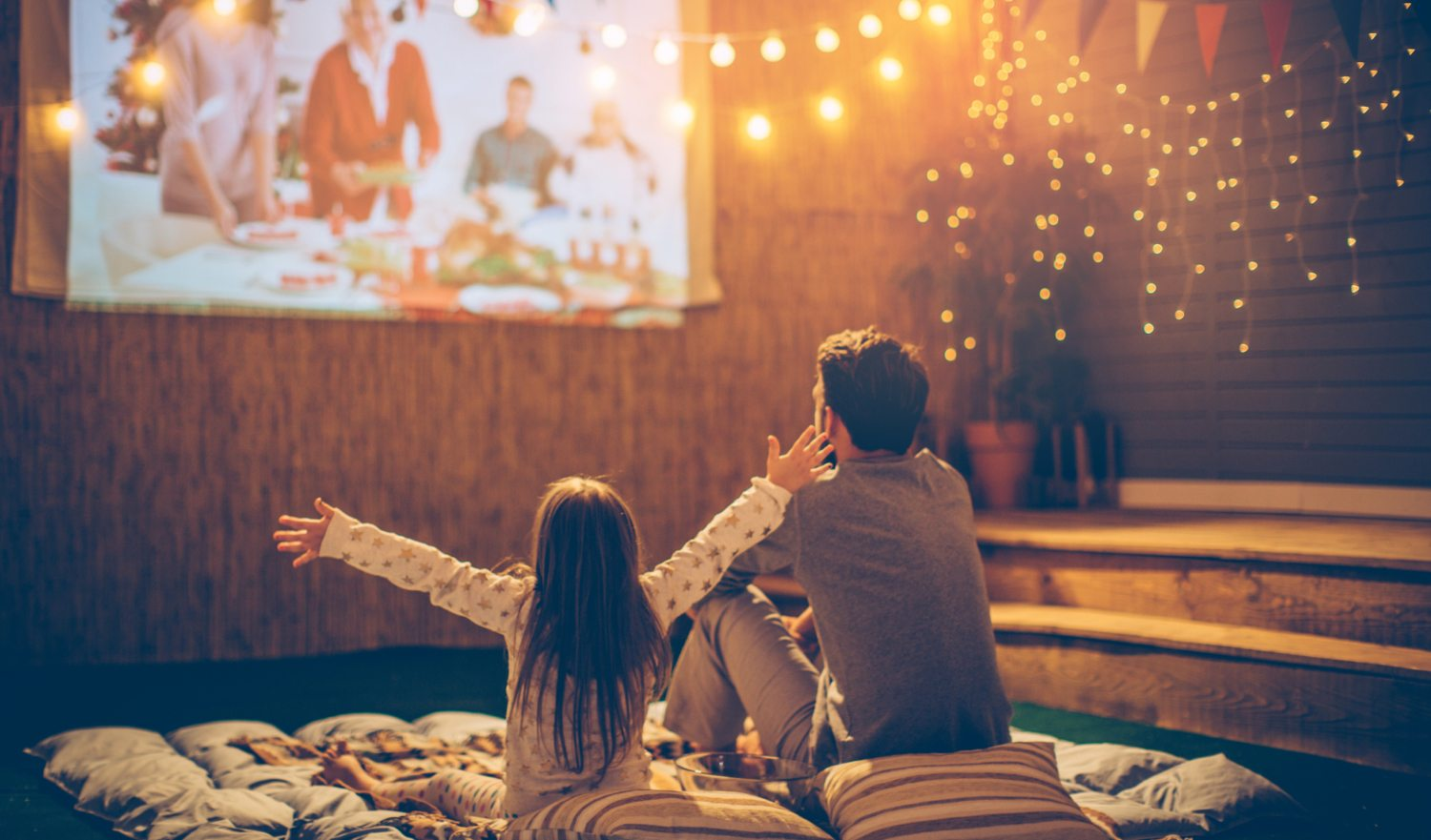 Father and daughter sitting at backyard and looking movie at home improved theatre. Backyard is decorated with string lighs.