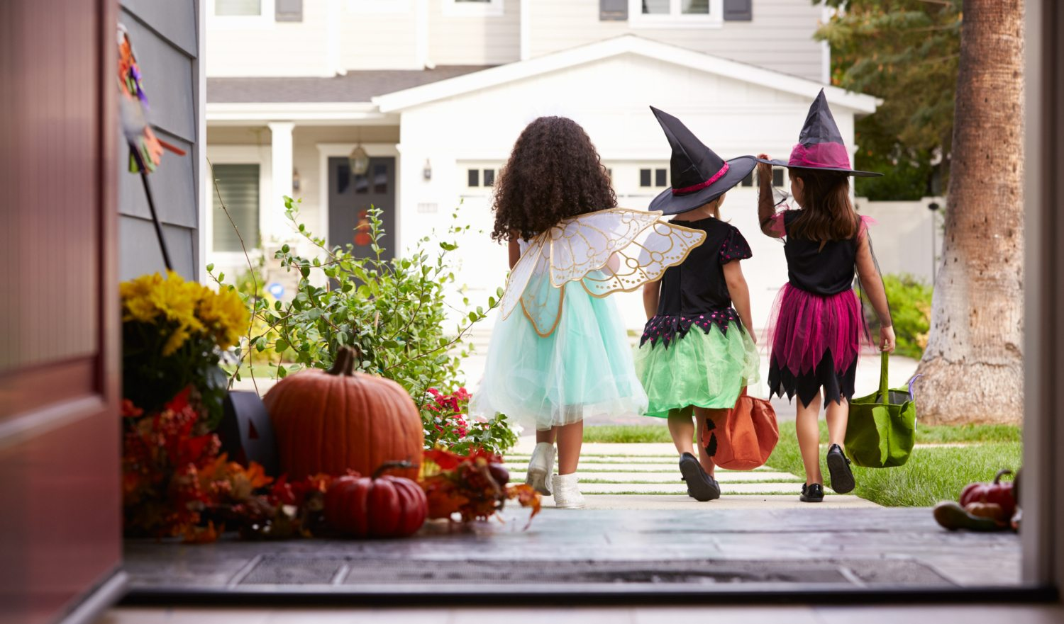 Three Children In Halloween Costumes Trick Or Treating