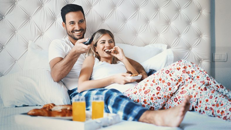 Closeup front view of a mid 20's happy couple watching tv in bed on lazy weekend morning. They are eating some snacks and having sodas. The guy is changing the channels.